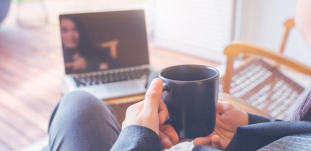 Рука женщины используют портативные компьютеры. она держит чашку кофе.