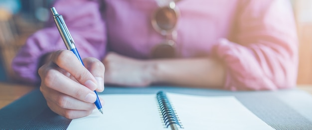 Рука женщины принимая примечания на тетради используя ручку.