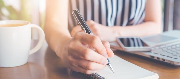 ビジネスの女性がペンでメモ帳に書いて、計算で働いています。