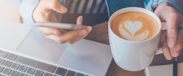 女性の手はコーヒーカップを保持し、電話を使用しています。