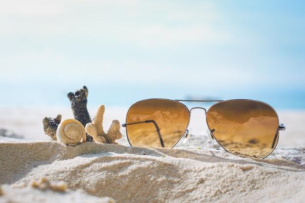Солнцезащитные очки и коралл на песке.