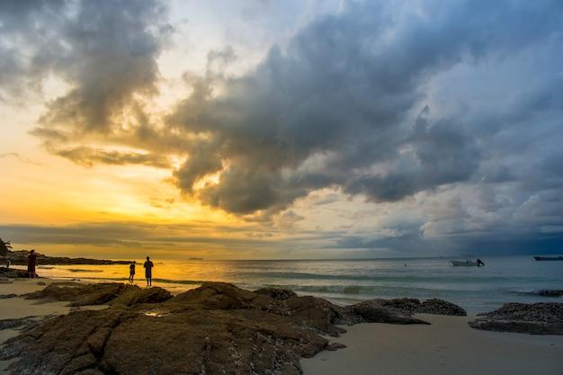 嵐が来ているときにビーチで朝に太陽を見ている人。