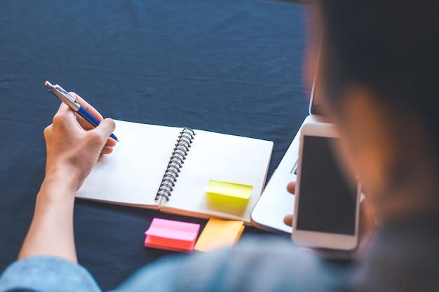 Женщина руку пишет на блокнот с ручкой в офисе.