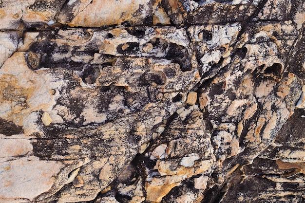 Шаблоны и текстуры старой вулканической скалы на пляже для фона