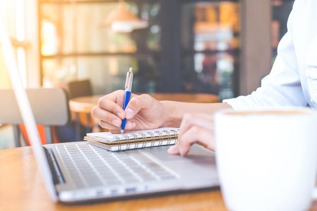 Рука бизнесмен работает на компьютере и пишет с ручкой на блокнот