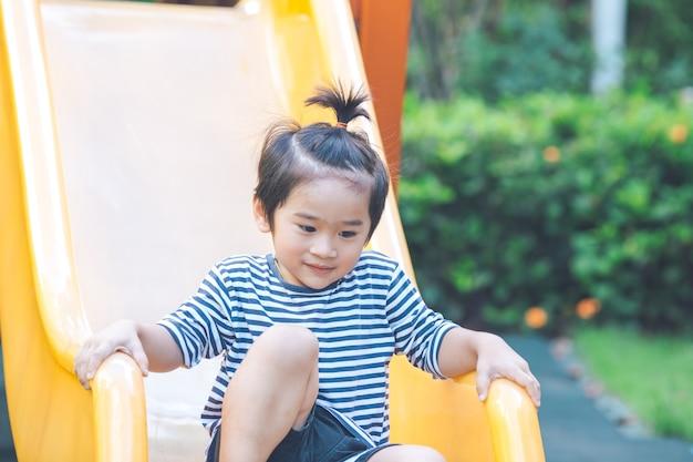 かわいい少年が遊び場でスライダーをプレイしています。