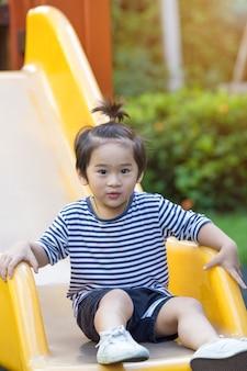 遊び場でスライダーをプレイしているかわいい男の子