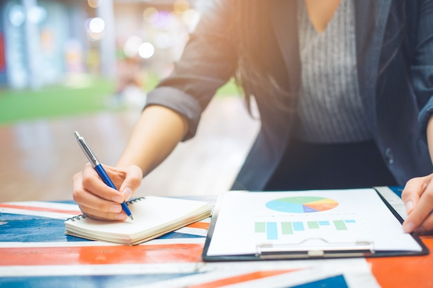 ビジネスの女性はビジネスの統計とグラフをメモします。