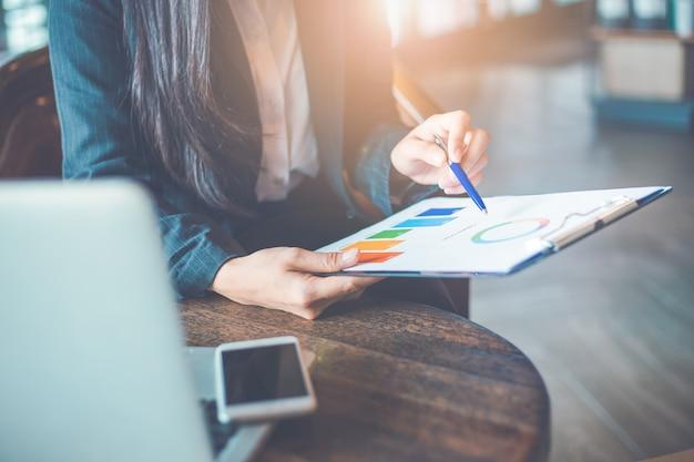 Женщина рука работать на диаграммы и графики, которые показывают результаты.