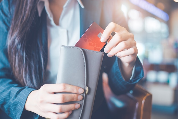 Женская рука используя кредитную карту, она вытащила карту из своего кошелька.