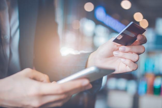 ビジネスの女性の手は、クレジットカードとスマートフォンを使用しています。