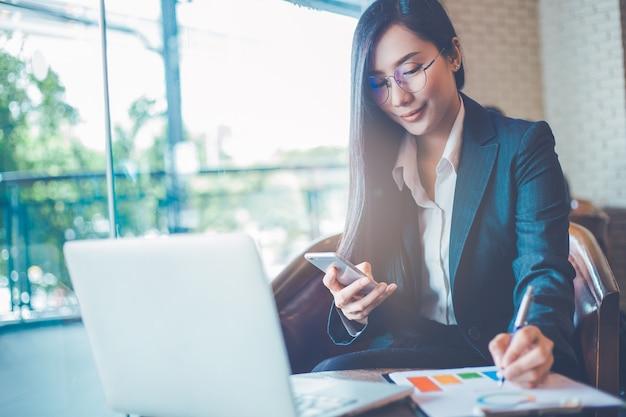 ビジネスの女性のアジア人はスマートフォンを使用し、チャートやグラフに書く