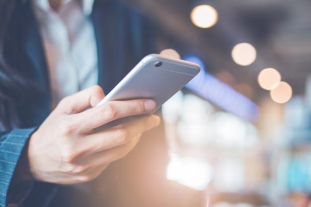 ビジネス女性の手はスマートフォンを使用しています。