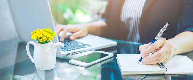 ビジネスの女性の手がペンでノートを書くと、オフィスでラップトップコンピューターを使用して