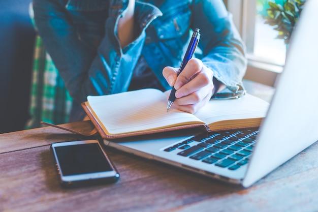 Женщина руки с записью пера на ноутбуке в офисе