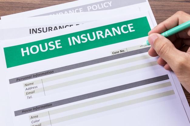 人の手でペンを持っている家の保険形態