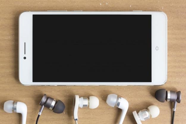 Смартфон и наушники на столе