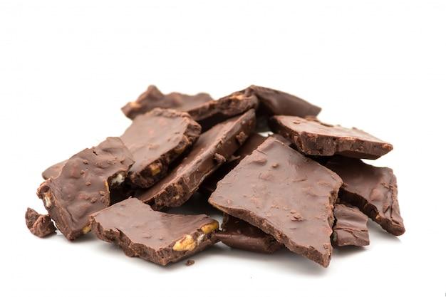 白い背景の上のナッツと壊れたダークチョコレート