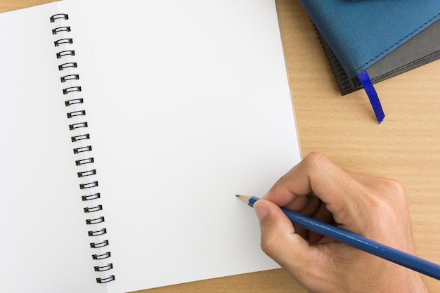 ノートブックの上に鉛筆で手