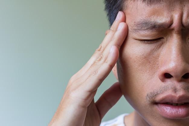 Человек с головной болью и падением плохой, сосредоточиться на пальце