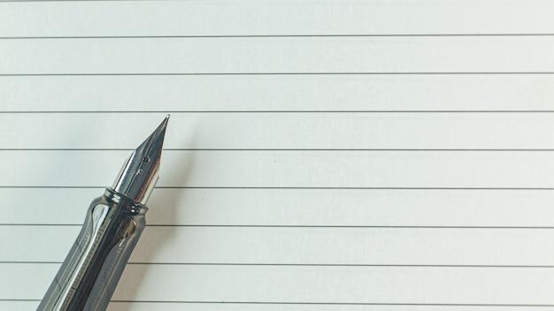 ビジネスコンテンツの木のテーブルに銀のペン。