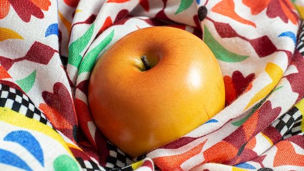 Яблоко на шарфе при слабом освещении для содержания пищи.
