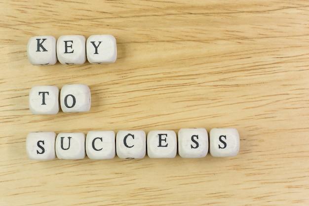 Ключ концепции к успеху на деревянном кубе для предпосылки.
