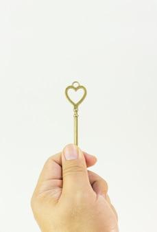 Изображение винтажного ключа золота в конце руки поднимающем вверх.