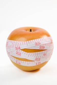 アップル&白い背景の上の測定テープ。