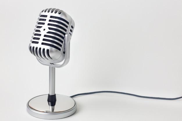 Изображение винтажного конца микрофона поднимающее вверх на белой предпосылке.