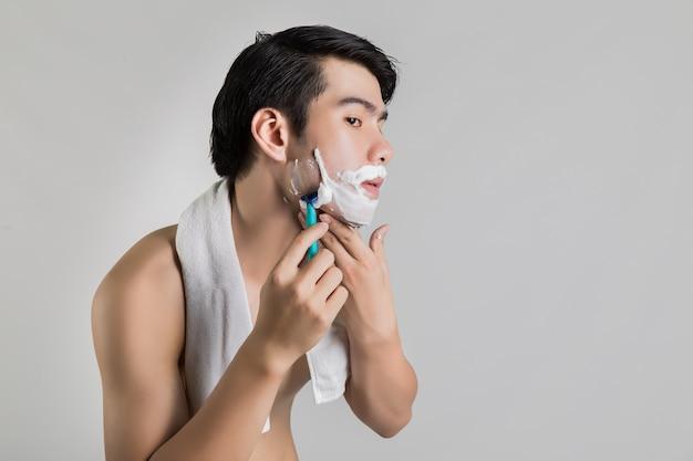 アジアのハンサムな男は遠くを剃っている