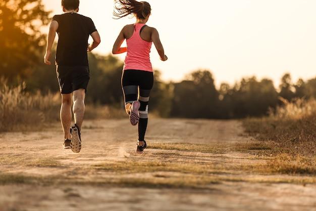 森林トレイルで走っている若いカップル