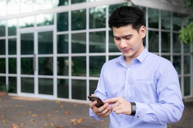 スマートフォンと屋外幸せな笑みを浮かべてアジアビジネス男
