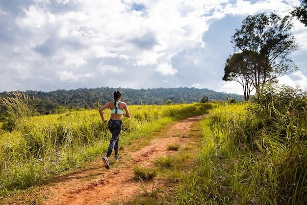 Азиатская молодая женщина фитнеса бежать на следе леса.