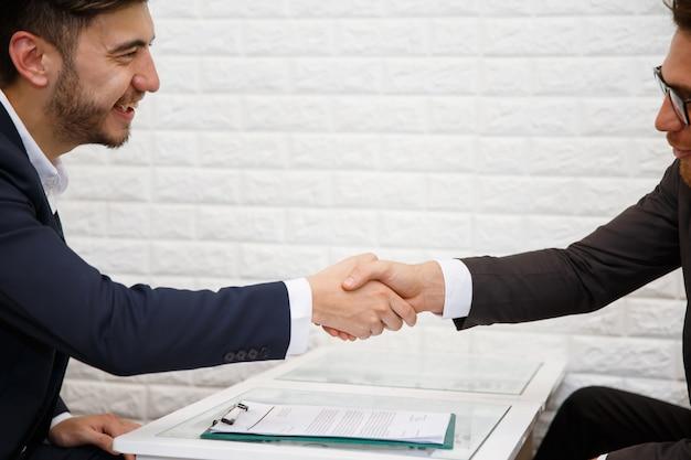 彼のパートナーとの契約を結ぶために握手するビジネスマン