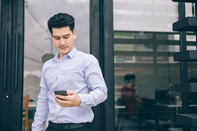 スマートフォンと屋外の幸せな笑みを浮かべてアジアビジネス男
