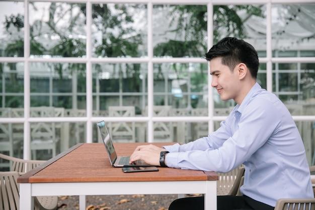 Счастливый улыбающийся азиатский деловой человек, открытый с ноутбуком