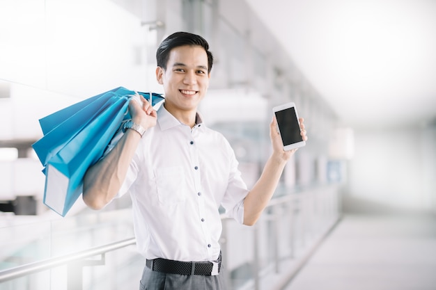 アジア人男性はショッピングモールでスマートフォンと買い物袋を持って買い物客です。
