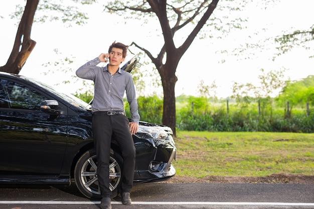 壊れた車のために携帯電話で話しているビジネスマン