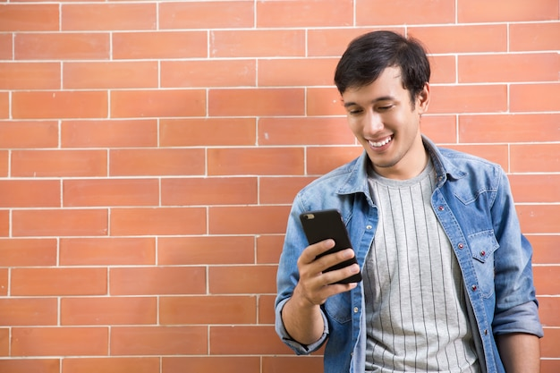Молодой счастливый человек улыбается, читая его смартфон