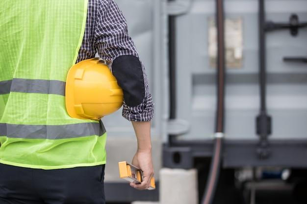 建設現場での労働者のセキュリティのための黄色いヘルメットを保持しているエンジニア