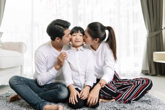 Азиатский семейный портрет с счастливыми людьми, улыбаясь смотреть на камеру в моем доме.
