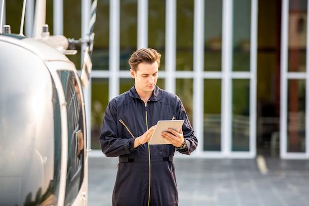 Коммерческий человек пилот в костюме техник, стоя перед вертолетом после проверки и обслуживания двигателя