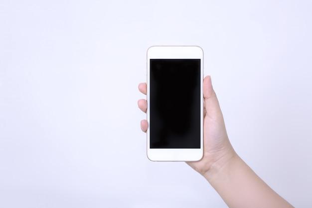 白い背景に対して携帯電話を持っている女性の手