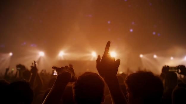 シルエットの群衆の人々がコンサートホールに手を