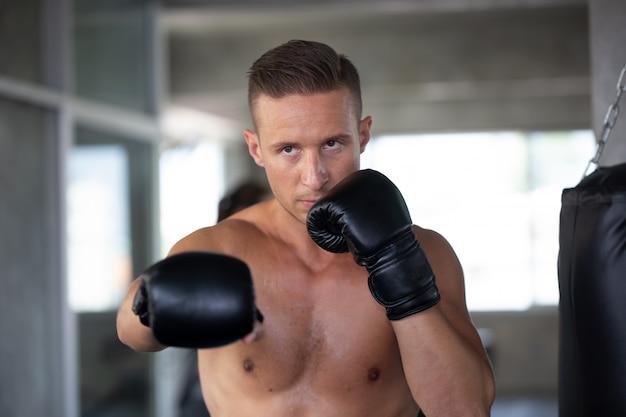 フィットネスジムでボクシンググローブを持つ若者
