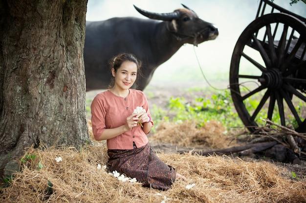 タイの伝統的なドレスと水牛を身に着けているアジアの女性。