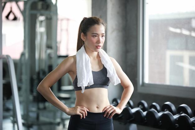 白いタオルを持つ女性は、フィットネスジムでのトレーニングの後、休憩を取る