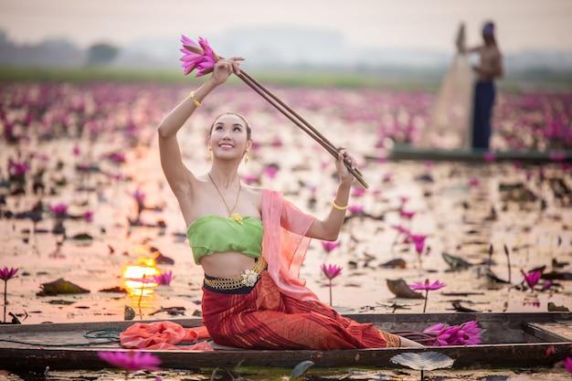 ボートの伝統的な衣装と池のピンクの蓮の花の若いアジア女性。伝統的な衣装の美しい女の子。タイ。文化的