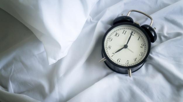 ホテルのベッドルームのベッドの目覚まし時計